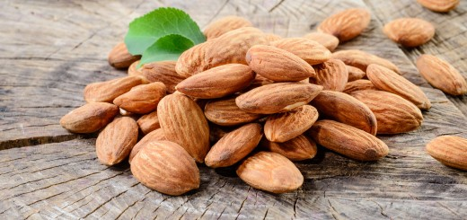 Almond. Nuts with leaves on wooden background
